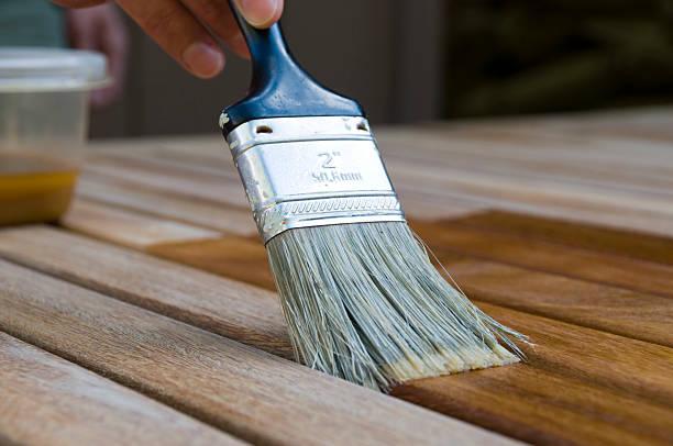 staining wood with paintbrush - houtbeits stockfoto's en -beelden
