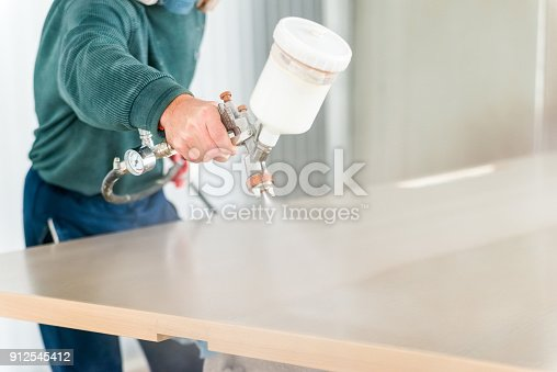 Close up worker's hand with spray gun applying paint on timber, wood coloring