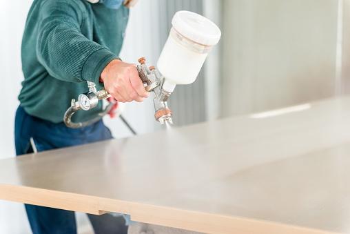 istock Staining wood with spray gun 912545412