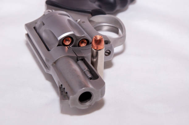 A stainless 357 magnum revolver with a single bullet next to it stock photo