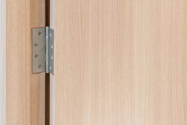 stainless door hinges on wooden swing door stock photo