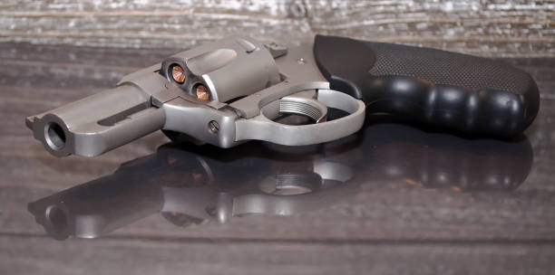 A stainless revolver on a reflective surface stock photo
