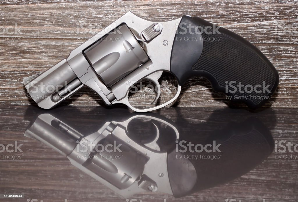A stainless revolver on a wooden background stock photo
