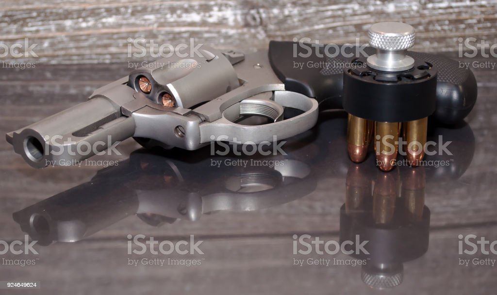 A stainless revolver with a loaded speed loader next to it stock photo