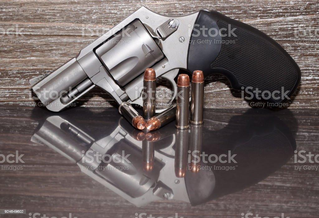 Un revólver de acero inoxidable con cinco balas al lado - foto de stock