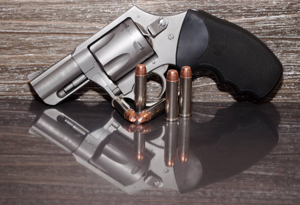 A stainless revolver with five bullets next to it stock photo