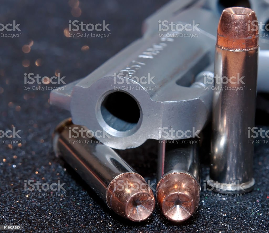 A stainless revolver with three bullets stock photo