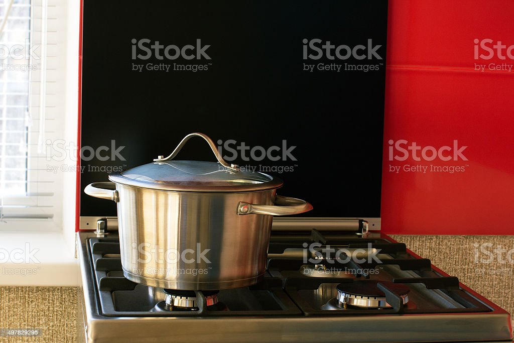 stainless saucepan on a gas stove stock photo