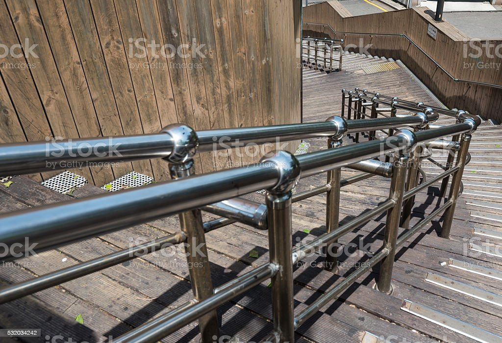 stainless steel banister with wooden staircase stock photo