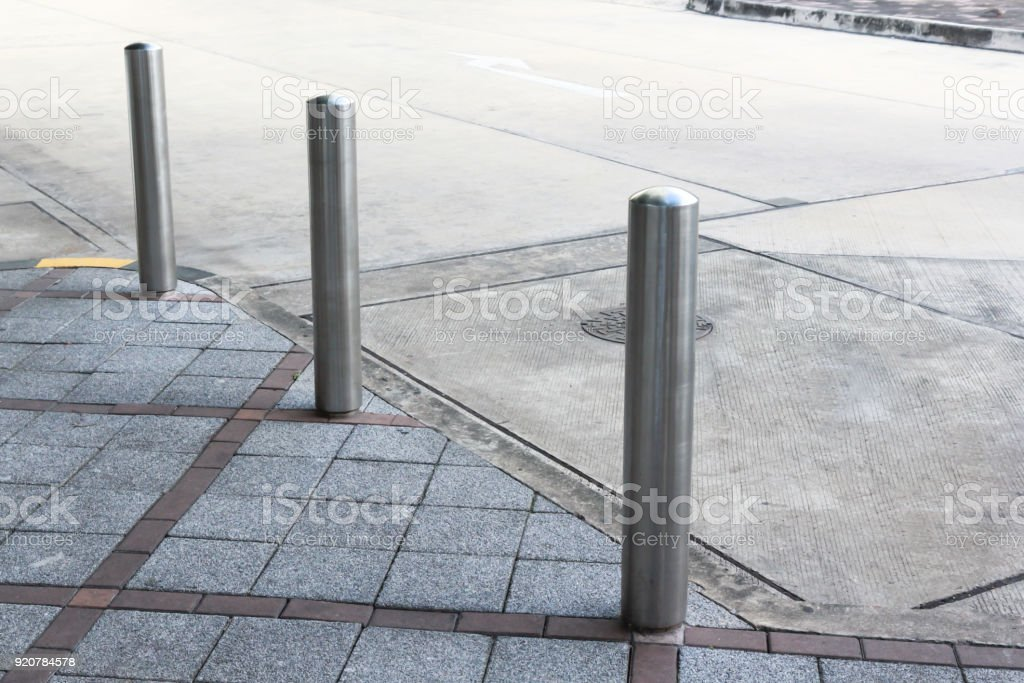 Stainless Steel bollards on grey stone pavement of car park stock photo