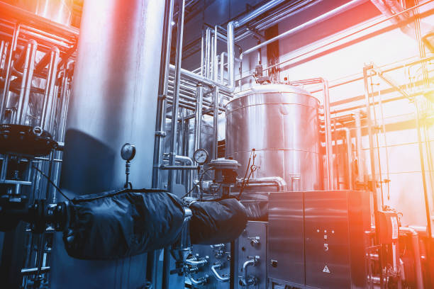 stainless steel brewing equipment : large reservoirs or tanks and pipes in beer factory. brewery production concept, industrial background in blue color and red lights - brewery tanks stock pictures, royalty-free photos & images