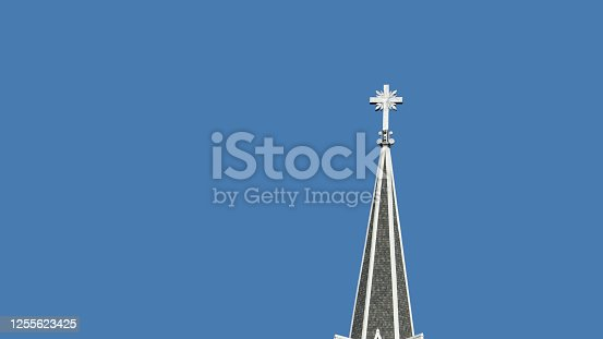 istock Stainless Steel cross on church steeple isolated on blue sky background. 1255623425