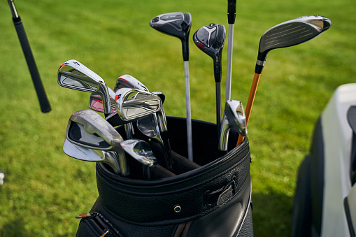 Close up of a complete set of different numbered golf clubs placed in a leather bag