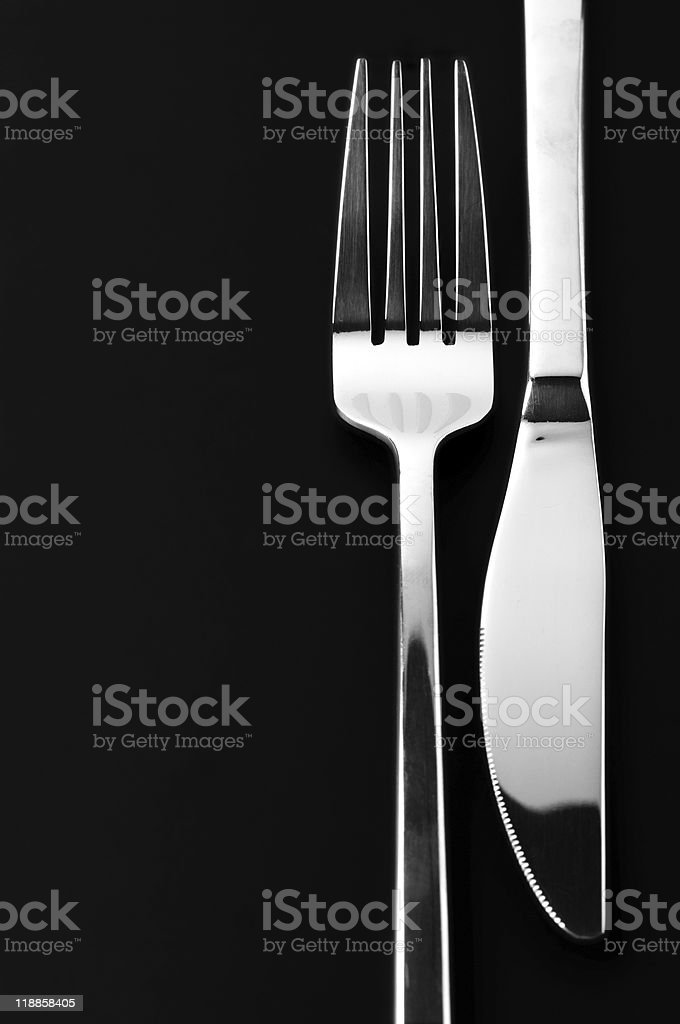 Stainless steel knife and fork against a black background stock photo
