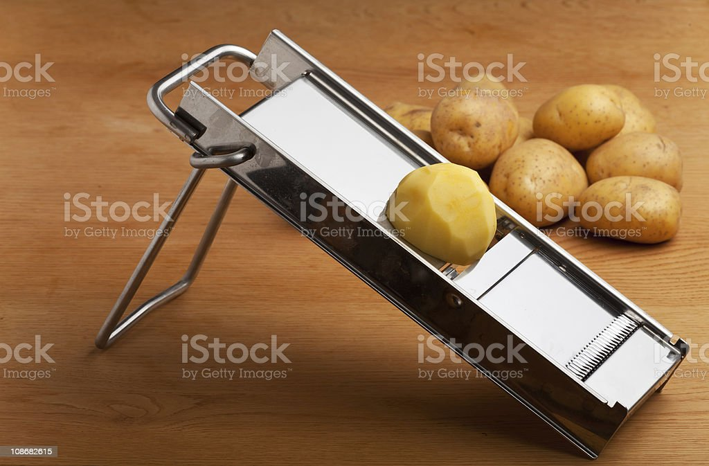 Stainless steel mandolin with half a peeled potato on top stock photo