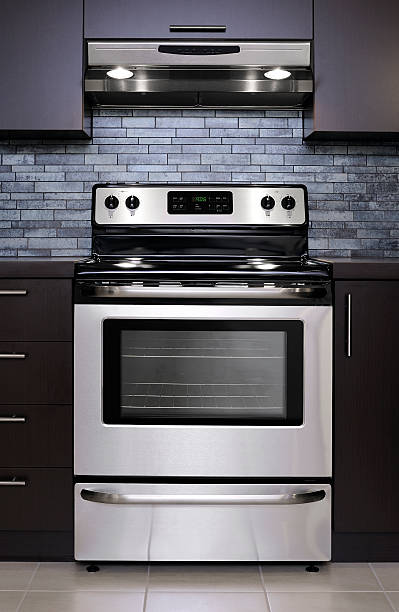 Stainless steel oven Stainless steel baking oven and range hood with lights on in a modern kitchen. More home interior and decor... oven stock pictures, royalty-free photos & images