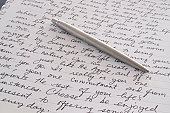 Stainless Steel Pen Laying on Written Page Letter