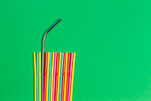 Stainless steel reusable drinking straw with plastic straws on green background.