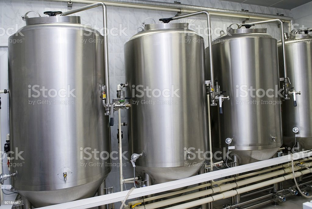 Stainless steel tanks line the wall in a clean environment stock photo