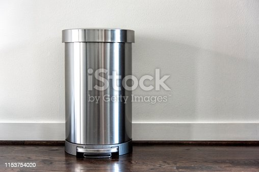 A contemporary stainless steel trash can atop a hardwood floor.