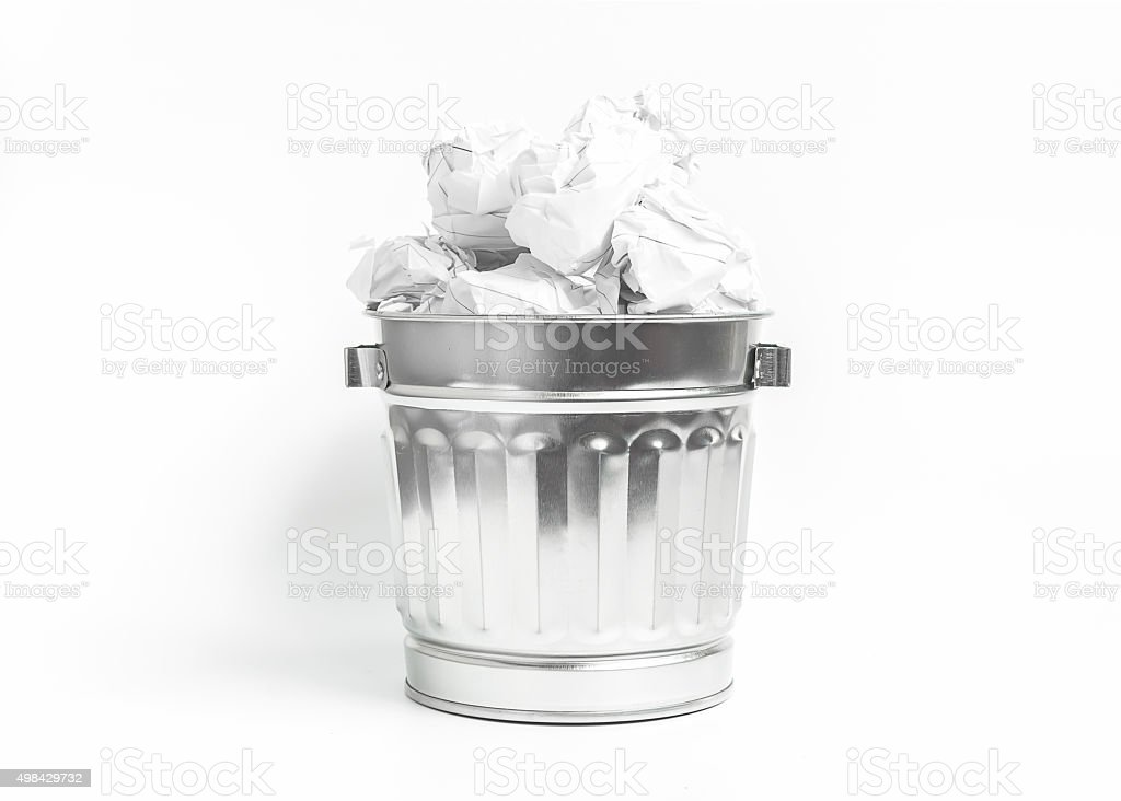 Stainless waste basket filled with crumpled paper on white backg stock photo