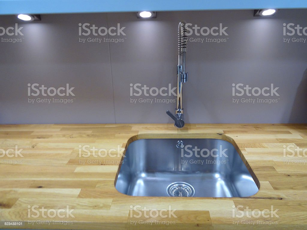 Photo showing a modern, stainless steel kitchen sink with a chrome...