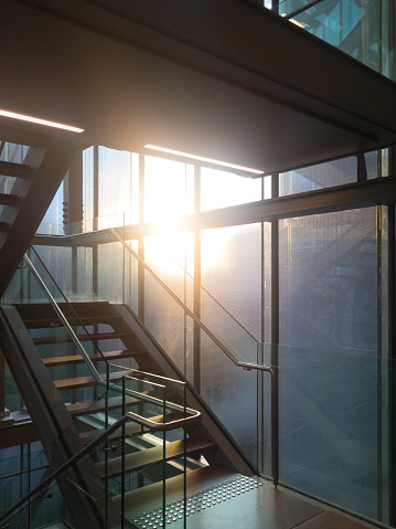 Sunset shot taken from inside a building showing the staircase back lit through glass windows