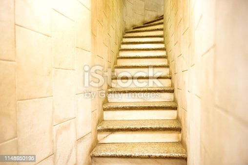Solid and steep narrow staircase between white marble walls.