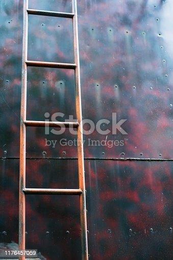 Staircase old vertical industrial metal rusted. on metal tank