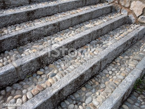 istock Staircase with steps built from round stones with cement and massive stone slabs around the edge 1066458040