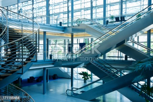 modern business building interior with stairs and escalators, blue tonedClick here to view more related images: