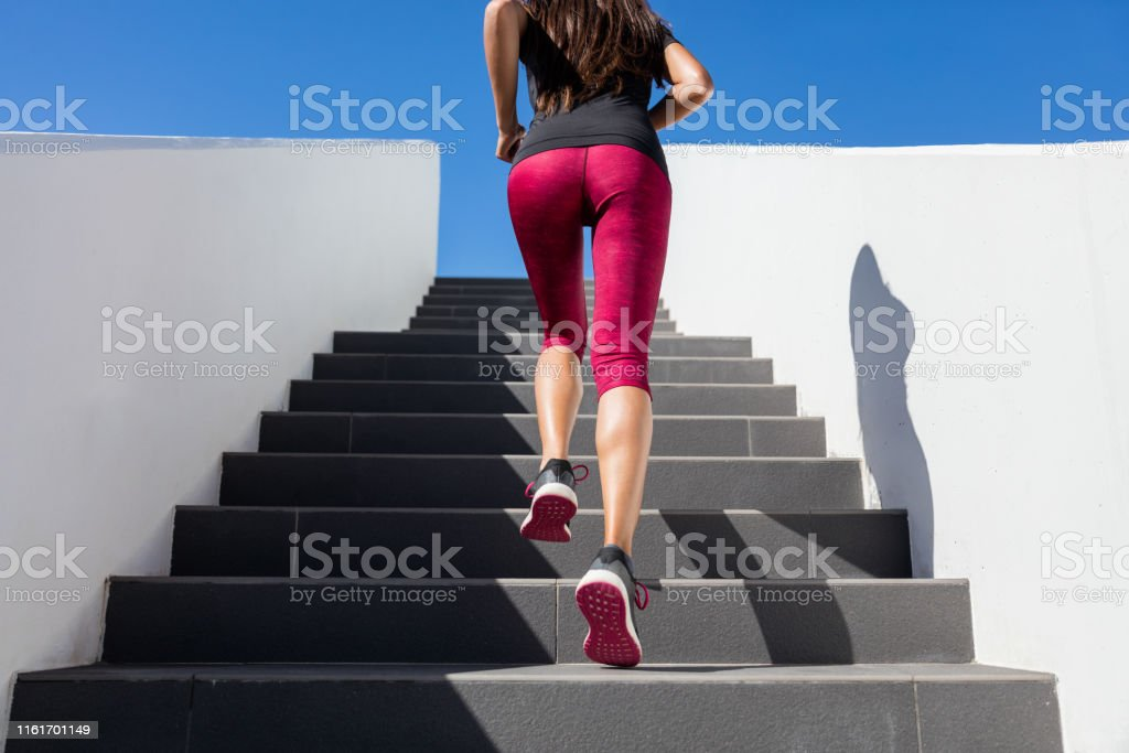 Stairs climbing running woman doing run up steps on staircase. Female...