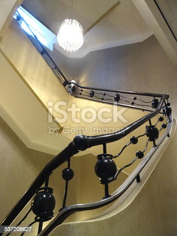 Photo showing angular stone stairs, painted white and leading to various landings.  This grand staircase features an ornate metal bannister, painted black.  The balustrading ironwork is typically art deco in style and is accompanied by a grand chandelier, while the carpet covering the steps features a pattern of brown and yellow circles.