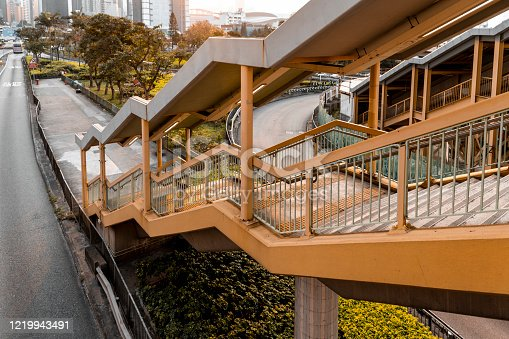 Stairs to footbridge above busy road in Hong Kong.