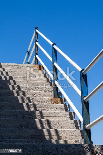 Simple concrete staircase outdoors with a diagonal shadow and a metal railing. Bright blue sky. Heraklion, Crete, Greece.