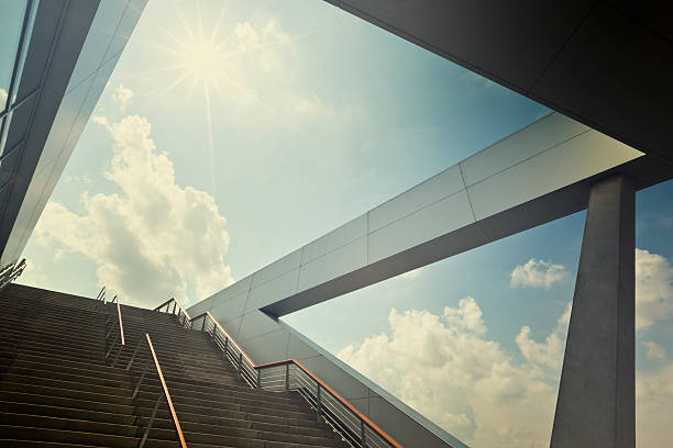 A stairway leading up to blue sky with sun over light cloud stock photo