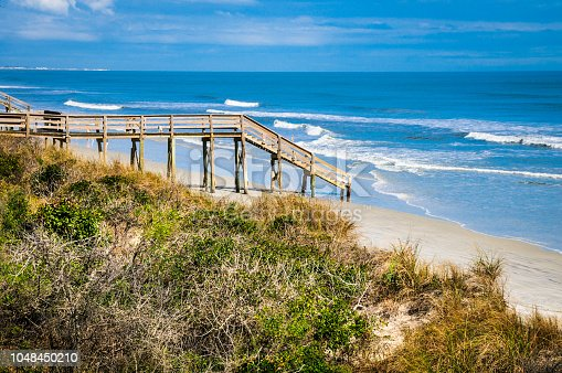 A wooden walkway and stairs lead to an empty beach in St. Augustine, Florida