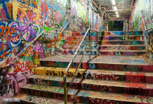 The Graffiti Tunnel at the University of Sydney, seen at night. A designated graffiti site for students of the university, colourful designs adorn the floor, surface and ceilings.
