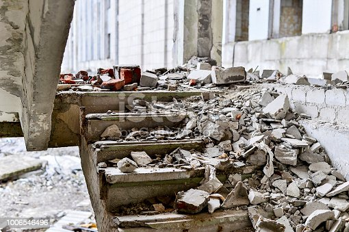 Stairwell concrete buildings littered with debris of stones and concrete.