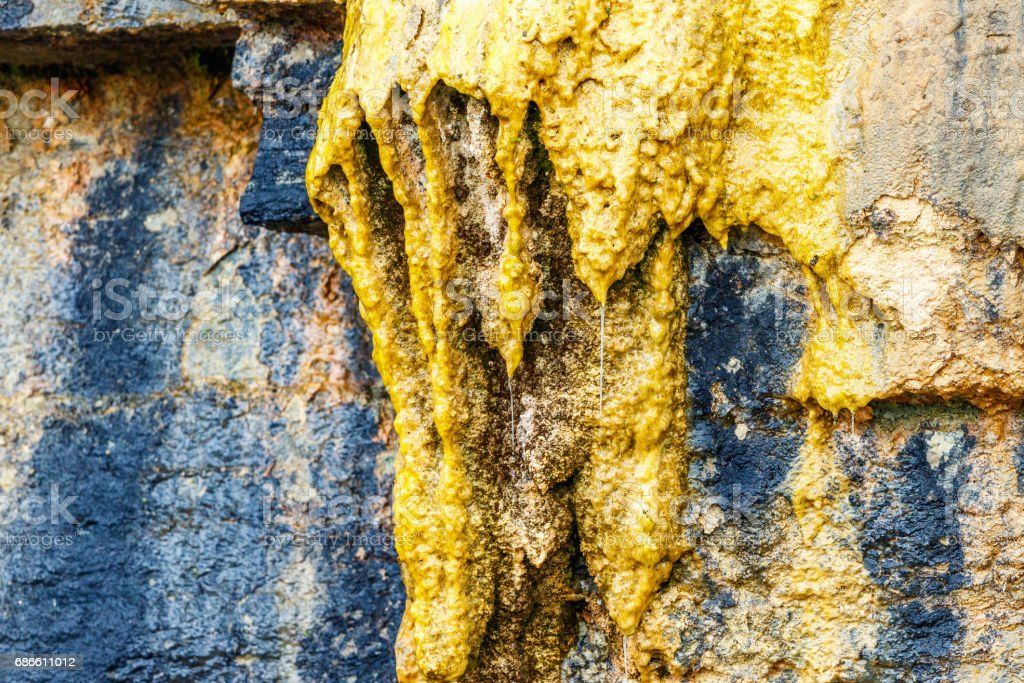 Stalactites on a rock wall with dripping water royalty-free stock photo