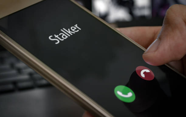 Stalker caller. A man holds a phone in his hand and thinks to end the call. Incoming from an unknown number at work. Incognito or anonymous, scammer or stranger stock photo
