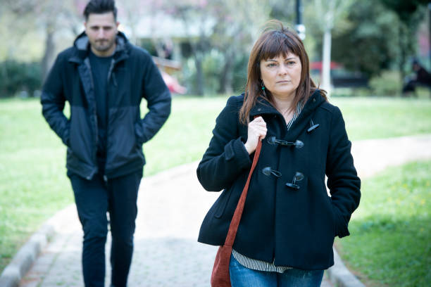 stalker follows woman in a park - stalking stock photos and pictures