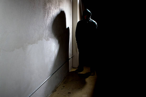 Stalker in a Dark Alley Photo of a hooded criminal stalking in the shadows of a dark street alley.  The hooded man is a silhouette and hiding in the dark.  The man is a criminal waiting to ambush victims.  The concrete walls provide copyspace.The photo depicts crime. alley stock pictures, royalty-free photos & images