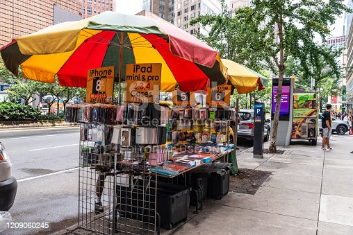 New York City, USA - August 3, 2018: Stall selling telephone and electronic accessories in the street with people around in Manhattan, New York City, USA