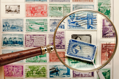 This images was rejected before for containing the American Red Cross logo, the name and logo have been removed from this image.  Old, cancelled stamps shown with Magnifying Glass & Tweezers used for the hobby of stamp collecting - a lot of great color and detail. The slight distortion on the edges of the stamp is from the distortion of the magnifying glass, the center of the Stamp is sharp.     http://i658.photobucket.com/albums/uu308/davidjames08/PostCards_Stamps-GreenTop.jpg