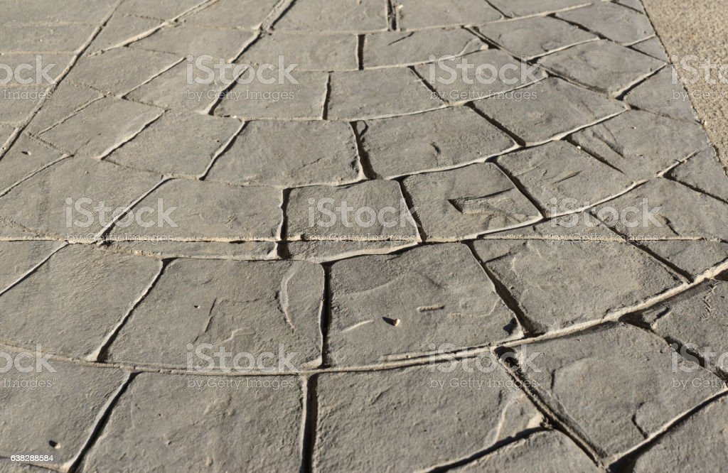 Stamped concrete pavement outdoor, mimics cobblestones circular pattern with waves stock photo