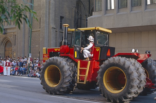Calgary, Alberta, Canada, 1981. The famous Stampede Parade through downtown Calgary. To see: Heavy tractor with driver,  spectators and buildings.