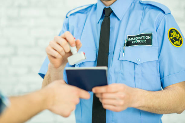 Stamping a Passport An unrecognizable immigration officer is in uniform. In this frame, he is stamping a passport allowing an unrecognizable person who is immigrating to enter into a new country. customs official stock pictures, royalty-free photos & images