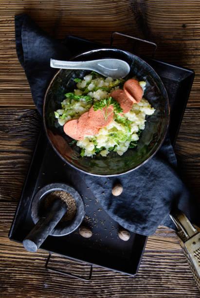 stamppot, traditionele hollandse maaltijd gemaakt van aardappelpuree en krul kool, geserveerd met worst schijfjes - stamppot stockfoto's en -beelden