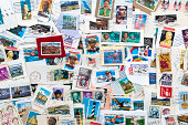 Collection of used U.S. stamps spanning several decades of U.S. postal history. Torn from envelopes.